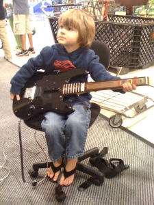 M playing Guitar Hero at Fry's